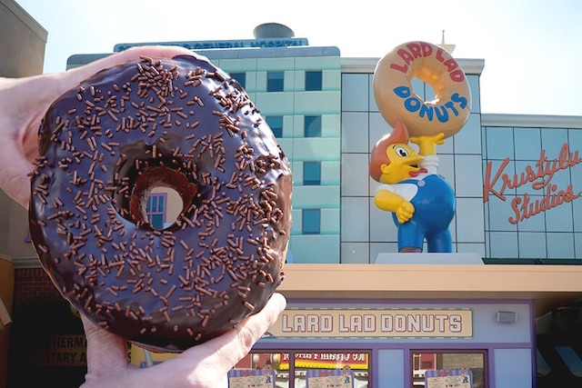Hands holding up a huge chocolate sprinkle donut in front of Lard Lad Donuts