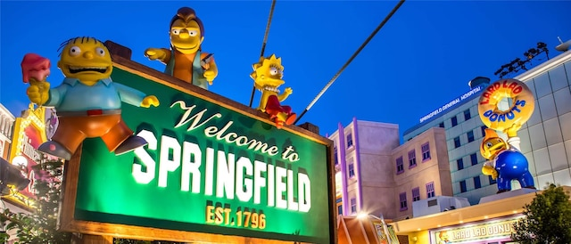 The Welcome to Springfield sign and Lard Lad Donuts are brightly lit under a night sky.